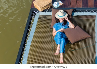 Advertising,Travel, Vacation, Time to relax, Holiday Concept - Top view of Beautiful asian woman lying  by the lake near the girl is suitcase, cup of coffee, map with copy space. It helped her relax.