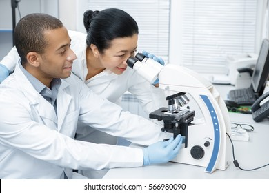 Advice from a colleague. Professional chemist senior woman looking through the microscope helping her younger male colleague with his research professionalism assistance experience study research
