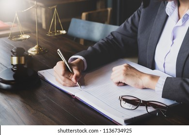 advice and justice concept. Justice scales and justice hammer and female lawyer use pen, working legal law at  lawyer office.