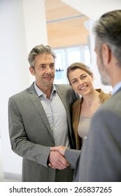 Adviser giving handshake to clients