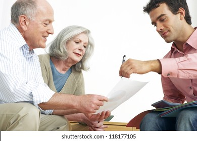 Advisor explaining paperwork to an elderly grey-haired retired couple seated on a couch