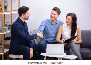 Advisor  Handshaking Young Couple After Signing Contract In Home