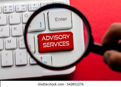 ADVISORY SERVICES word written on keyboard view with magnifier glass