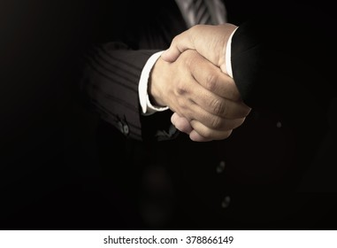 Advocacy concept: Two successful business men shaking hands after good deal