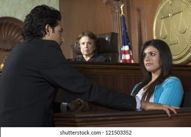 Advocate with witness and judge sitting in the background