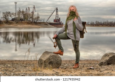 Adwenturer steampunk traveler girl or wooman in half face mask from neckerchief scarf, with vintage telescope in hand and a backpack, stays on rock near the river. HDR image