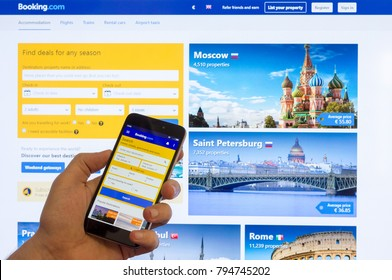 Adygea, Russia - January 16, 2018: The home page of the Internet booking of hotels booking.com on the screen the Chinese Xiaomi smartphone in male hand on a computer monitor