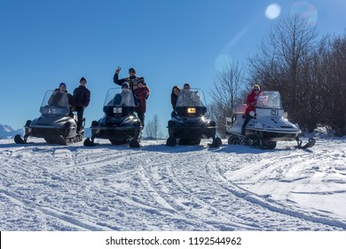 Adygea, Russia - January 23,  2017: Young happy men, women and children on the snowmobiles Yamaha on a snowy slope winter Sunny day