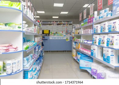 Adygea, Russia - June 6, 2018: cotton pads, wet wipes, diapers for adults, absorbent diapers and water bottles on the shelves and counter with medicines and other medicines in the pharmacy minimarket