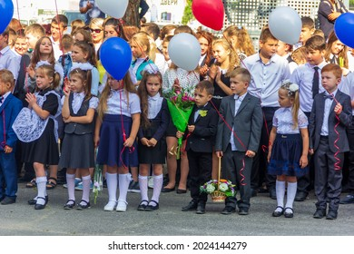 Adygea, Russia - September 1, 2019: first-graders with bouquets of flowers and balloons at school at a solemn ceremony on the day of knowledge
