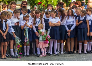 Adygea, Russia - September 1, 2019: schoolchildren are standing on the solemn line on the day of knowledge, and a little girl is crying and clinging to her sister