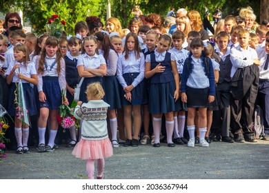 Adygea, Russia - September 1, 2019: schoolchildren are standing on the solemn line on the day of knowledge, and a little girl goes to her sister