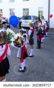 Adygea, Russia - September 1, 2020: first-graders with bouquets of flowers and balloons at school at a solemn ceremony on the day of knowledge