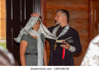 Adygea, Russia - September 23, 2017: an Orthodox priest confesses a woman, covering her head with an epitrachil absolves her of her sins