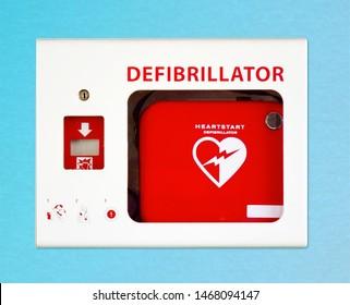 AED cardiac defibrillator on blue wall