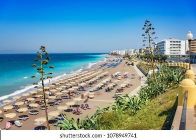 Aegean beach with sunshades in city of Rhodes (Rhodes, Greece)