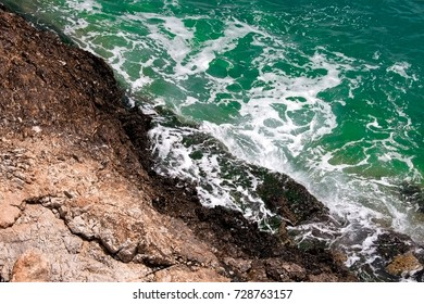 Aegean sea with green waters and rocks. Splashes and foam.