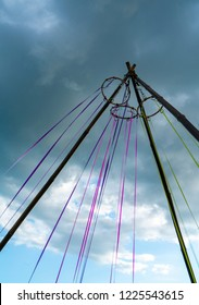 An aeolian device creating natural music as wind vibrates across red, green and blue ribbons on a stormy day. Ribbons are tensioned on a tripod with rings at the top and the fixings on the ground.