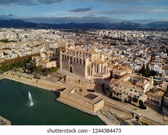Aerial above drone view Palma de Mallorca Cathedral was built on a cliff rising out of the sea. Picturesque panorama Majorca city scape mountain range cloudy sky residential buildings from top. Spain