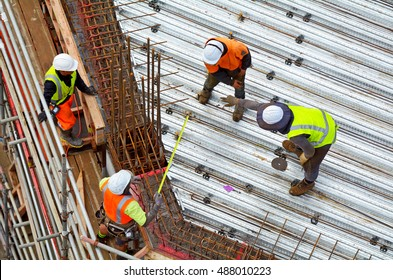 Aerial above high angle view of unrecognized civil engineer supervise roof construction workers work in a construction site. Building development concept. Real people. Copy space