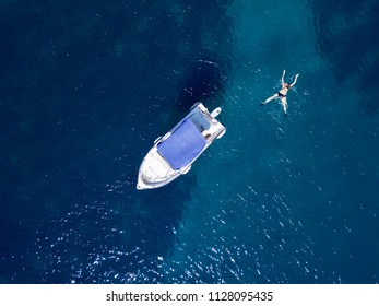 Aerial above swimmer and small boat in shallow tropical sea