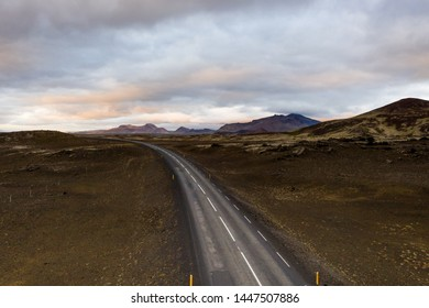 Aerial above view of empty icelandic road leading to sunset and mountains