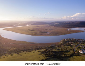 Aerial above a winding river in a wetland at sunrise