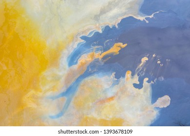 Aerial abstract pattern of colorful water and mud, nature pollution by copper rmine chemicals viewed from a drone
