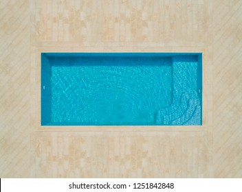 Aerial abstract view of empty swimming pool with tiled area.