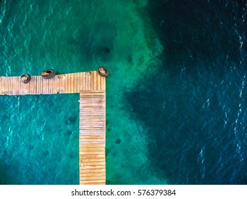 An aerial abstract view of a marina wooden pier in a shallow turquoise sea water. Sparse composition with lots of space to add copy (text).