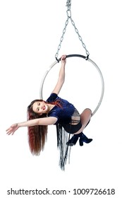 Aerial acrobat in a hoop. Young happy girl performs the acrobatic elements in the air ring. Studio shooting, isolated on white background.
