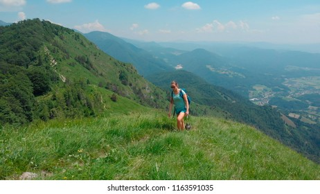 AERIAL: Active girl and her fit dog hike up a grassy mountain overlooking the spectacular green valley. Breathtaking mountain range surrounds female trekker ascending a grassy hill with black dog.