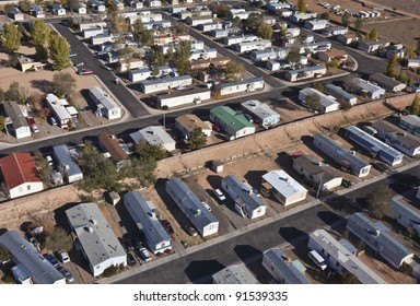 Aerial of aging mobile homes in bright desert sun.