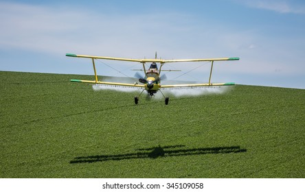An aerial applicator/crop duster sprays a field of wheat to help maximize the productivity of the crop while eliminating invasive weeds and disease from the wheat crop.