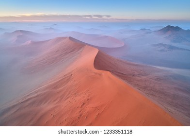 Aerial, artistic photo of dunes of Namib desert covered on mist. Famous orange dunes of Namib from above. Desert landscape. Sunrise in Namib desert. Travel photography, Namib-Naukluft National Park.