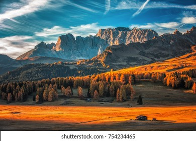 Aerial autumn sunrise scenery with yellow larches and small alpine building and Odle - Geisler mountain group on background. Alpe di Siusi (Seiser Alm), Dolomite Alps, Italy.