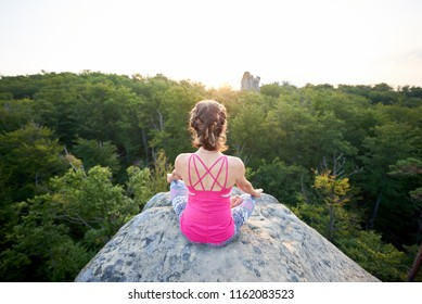Aerial back view of young slim tourist woman in pink top sitting on big mountain rock, doing yoga at sunrise on green trees tops forest background. Sport, gymnastics and fitness concept. Siddhasana