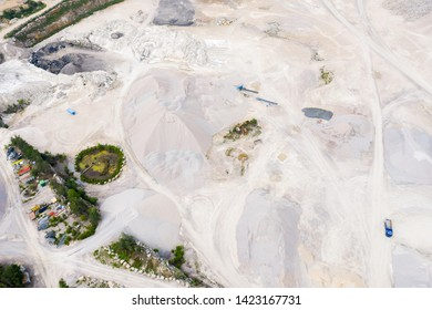 Aerial of bare and desolate stone quarry landscape. A truck is visible on the ground and gives scale to the size.