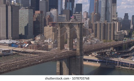 AERIAL: Beautiful cityscape of iconic downtown New York City skyscrapers, office buildings and financial district high-raise towers. Busy Brooklyn Bridge highway with cars and semi trucks on sunny day