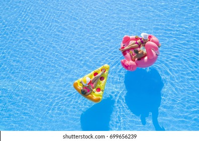 AERIAL Beautiful couple & attractive girl enjoying fun colorful floaties in pool