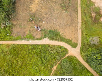 Aerial bird eye view of excavator clearing forest land for development.