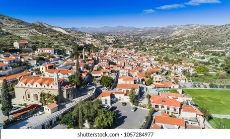 Aerial bird eye view of Kalavasos village valley, Larnaca, Cyprus. A traditional town with ceramic roof tiles houses, a greek orthodox christian church and muslim mosque around hills, from above.
