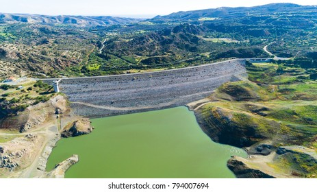 Aerial bird eye view of Kalavasos rockfill dam wall, Larnaca, Cyprus. The street bridge over the reservoir crossing Vasilikos river and the hills around the water from above.