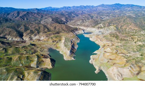 Aerial bird eye view of Kalavasos rockfill dam, Larnaca, Cyprus. The Vasilikos river streaming towards the reservoir, the mountainous landscape and the hills around the water from above.
