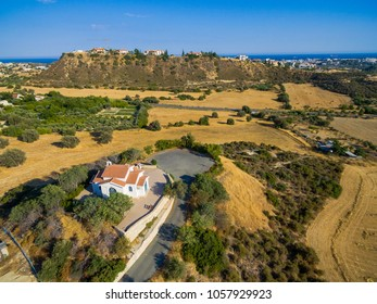 Aerial bird eye view of Saint George chapel (parekklisi Agiou Georgiou) in Germasogia municipality, Limassol, Cyprus on a hill by the sea inside hay fields at summer. A christian greek orthodox church