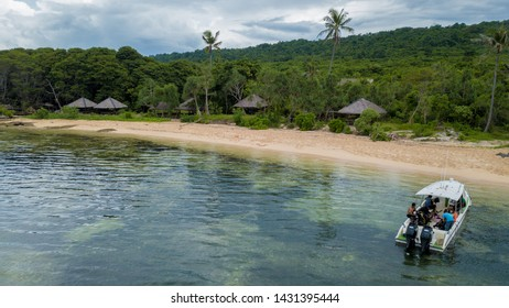Aerial / bird view of the beach with a boat that is docked and nice blue ocean in Wakatobi, Indonesia, Asia
