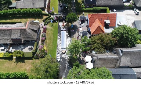 Aerial bird view photo busy canal in Giethoorn is town in province of Overijssel Holland and is often referred to as the Venice of the Netherlands because of the popular canals with tourist tour boats