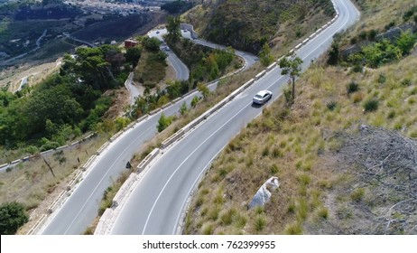 Aerial bird view photo of car over mountain pass navigable route through mountain range traffic driving over hairpin turn and climbing steep over ridge mountain pass make use of gap saddle col