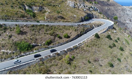 Aerial bird view photo of cars over mountain pass navigable route through mountain range traffic driving over hairpin turn and climbing steep over ridge mountain pass make use of gap saddle col