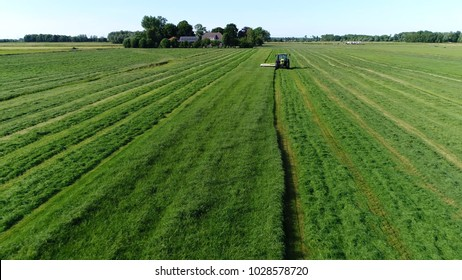 Aerial bird view photo farm scene tractor mowing grass drone flying backwards in front of agricultural machinery showing the bright green grass and in background a typical dutch farm with living area